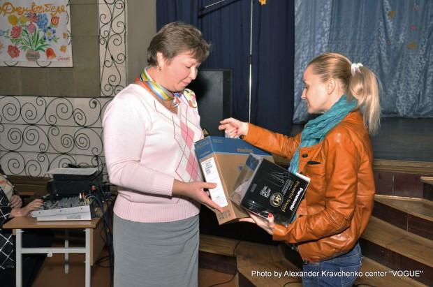 Оксана Рева (справа) от имени оргкомитета «КОНТИНЕНТа талантов» передает подарки (ноутбук и наушники) педагогу-организатору интерната.